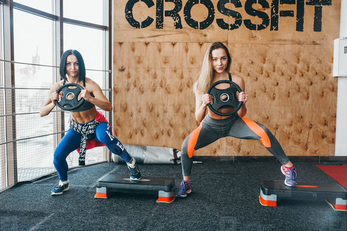 Two beautiful girls together in a fitness room