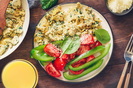 Breakfast table with a portion of spinach scrambled eggs served fresh vegetables Healthy and fitness eating concept
