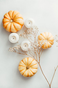 Flat lay composition of small pumpkins on a white background with decor  The concept of Thanksgiving and Fall time