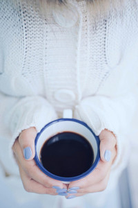 Top view and close up woman hands holding hot cup of coffee or t