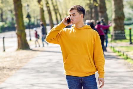 Young urban man using smartphone walking in street in an urban park in London