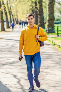 Young urban man using smartphone walking in street in an urban park in London