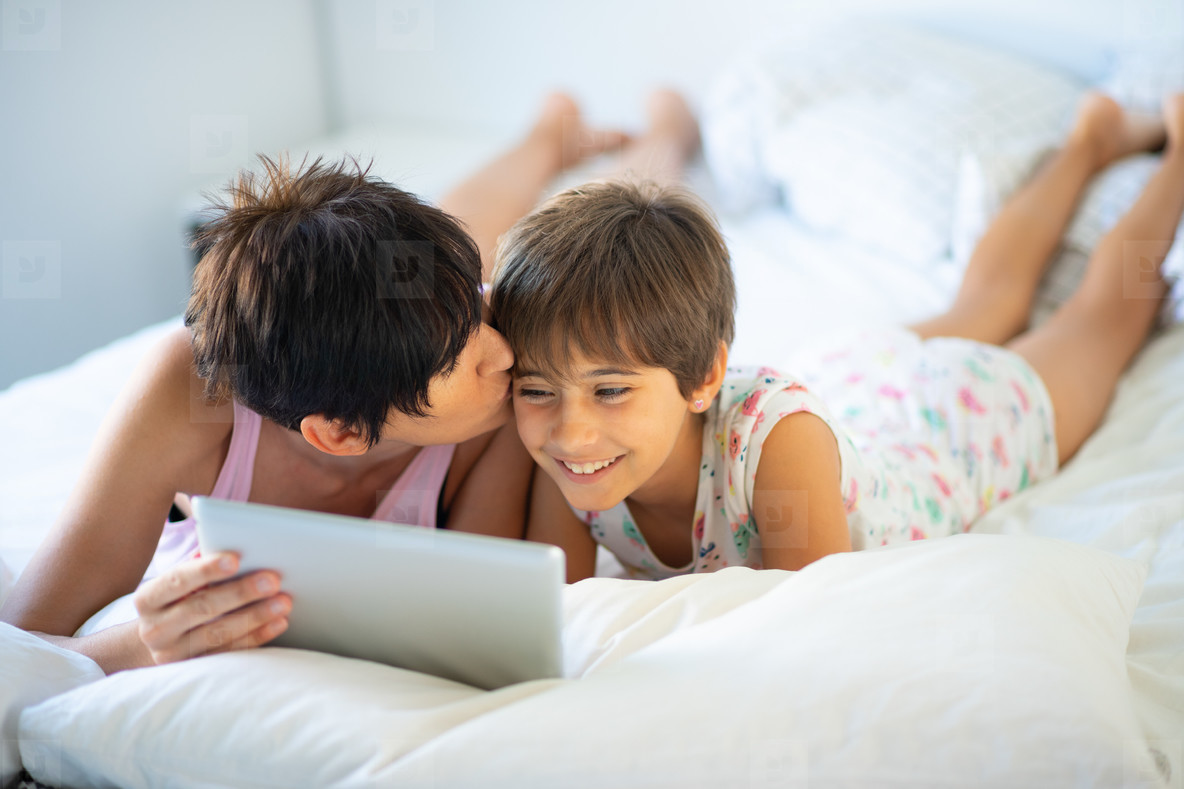 Middle age mother with her eight years daughter using digital tablet in bedroom