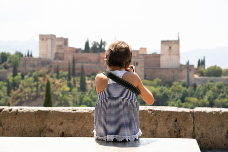 Little girl making photo with DSLR camera to the Alhambra