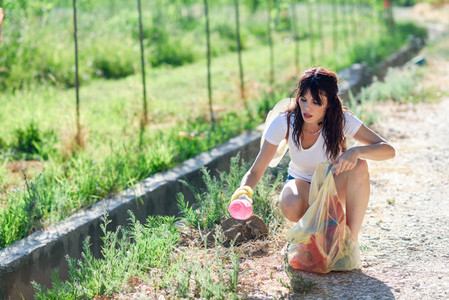 Woman hand collecting garbage of the grass in the countryside