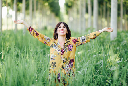 Woman arms raised enjoying the fresh air in green forest