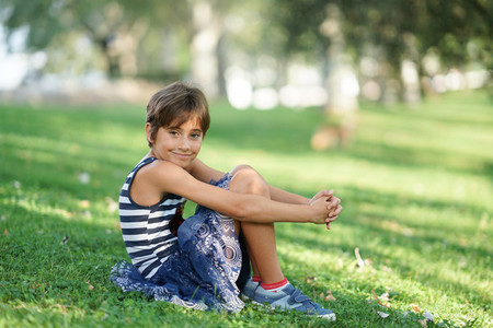 Little girl  eight years old  sitting on the grass outdoors
