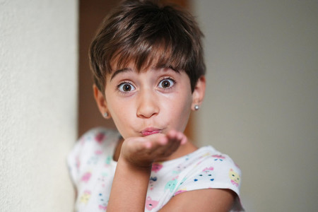 Funny little girl  eight years old  blowing a kiss