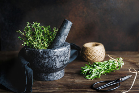 Fresh herbs in a marble mortar on a table Rustic style food photography