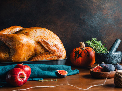 Festive table for Thanksgiving Holiday with whole roasted turkey with apple pumpkin figs and herbs in a mortar