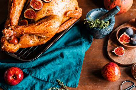 Top view of a festive table for Thanksgiving Holiday with whole roasted turkey with apple  pumpkin  figs and herbs in a mortar