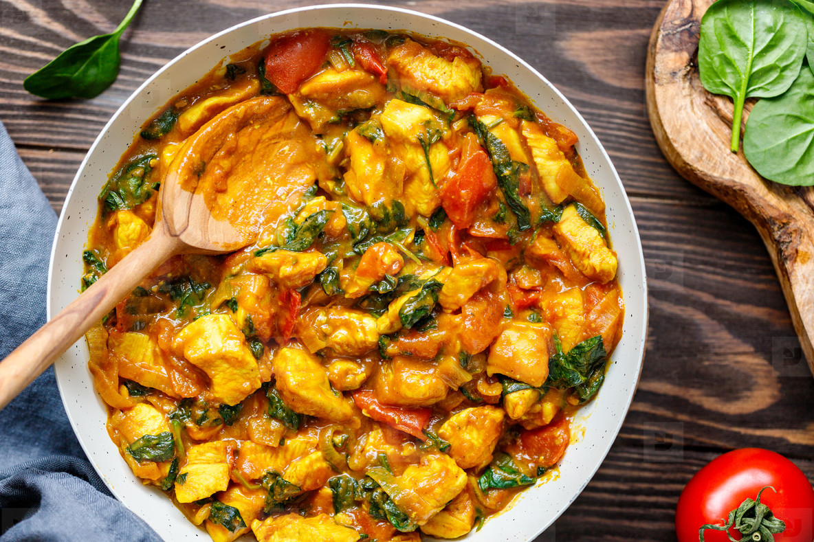 Top view on Bombay chicken curry with spinach  tomato and onion in a white frying pan on a kitchen wooden table  Indian traditional cuisine