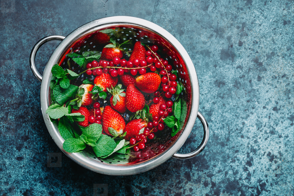 Metal colander with fresh berries above blue background  Strawberry  blueberry  red currant  Top view  summer concept