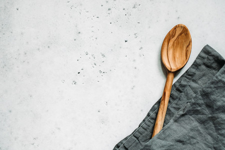 Wooden spoon and grey linen napkin