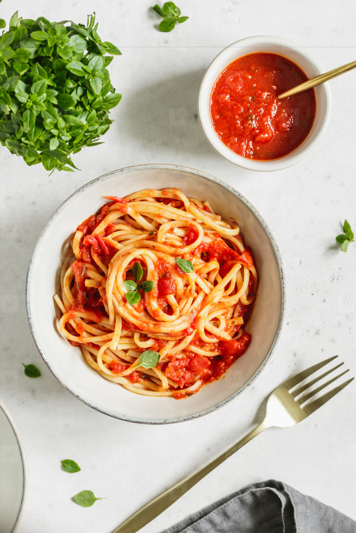 Top view of traditional pasta with tomato and Greek basil sauce in a ceramic bowl on a white table