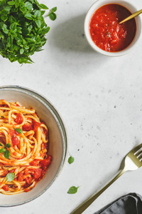 Preparation of traditional pasta with tomato and Greek basil sauce on a white table  top view  copy space