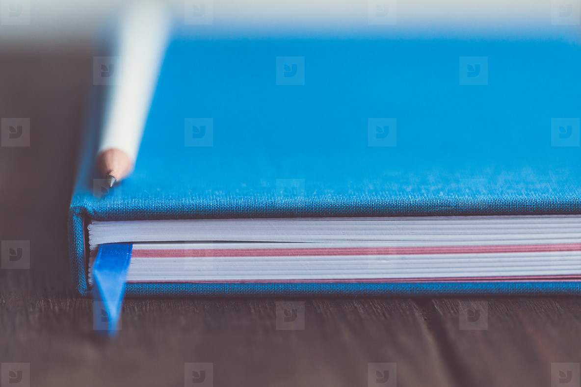 Lifestyle photo of closed blue paper notebook with white pencil on a wooden table in a workspace