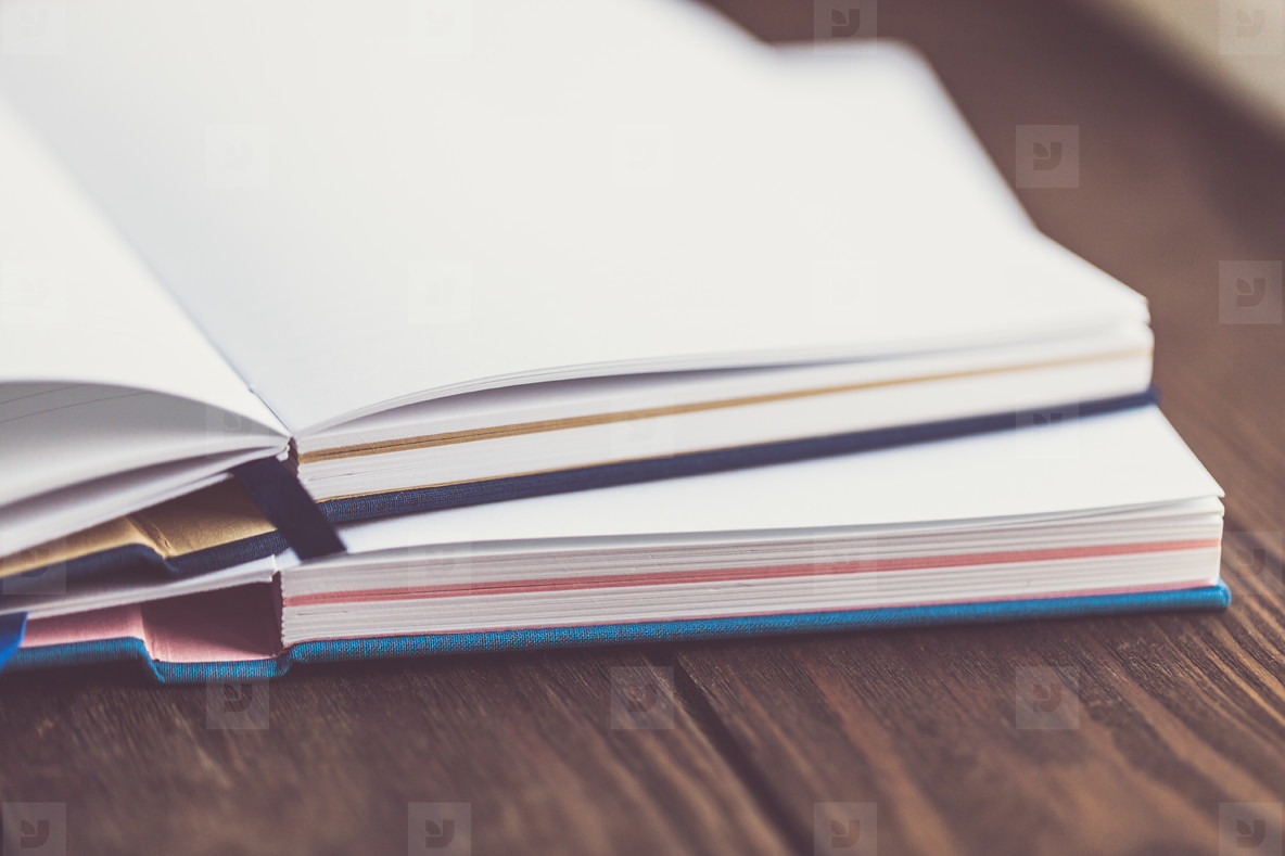 Lifestyle photo of an empty open paper notebooks  on a wooden table in a workspace