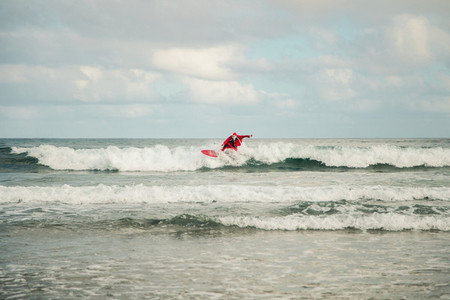 Young man surfer dressed as Santa Claus on the beach