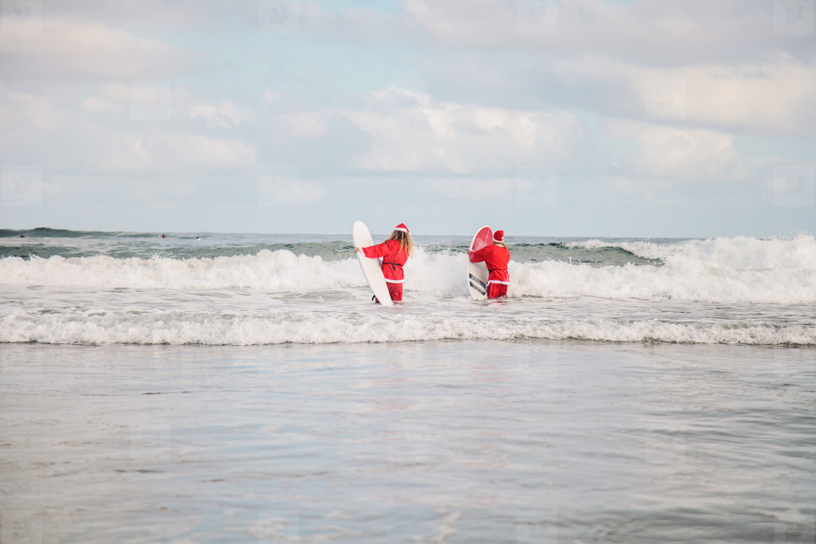 two surfers dressed as Santa Claus on the beach