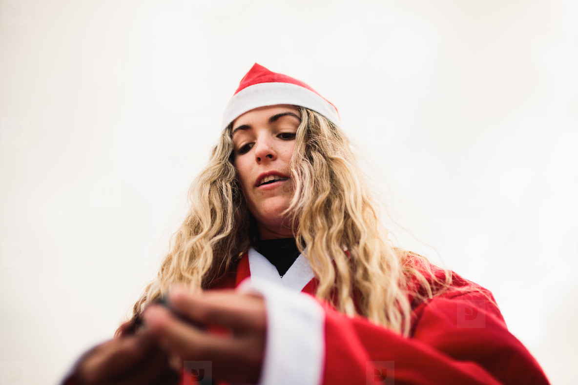 Young blonde dresses up Santa Claus on the beach