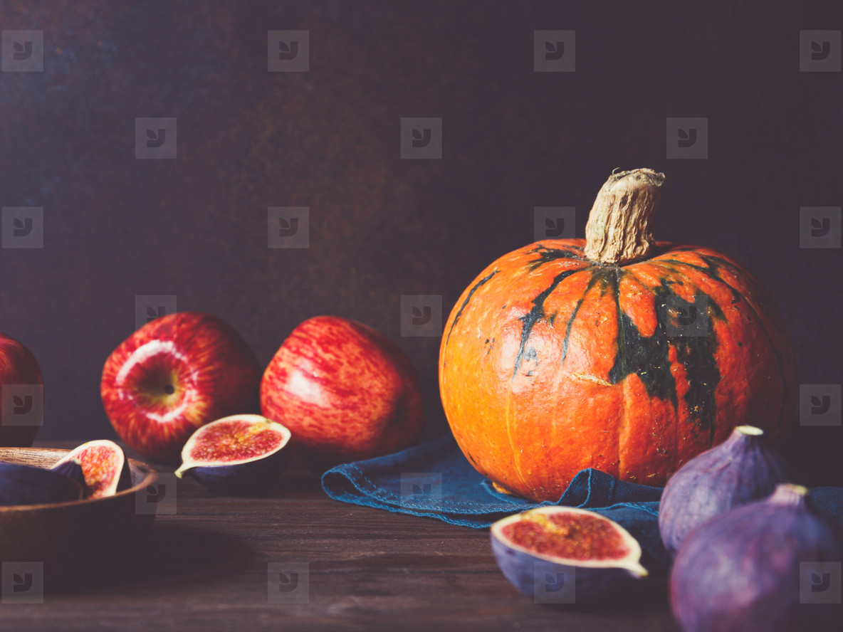 Autumn food still life with season fruits and vegetables like pumpkins  red apples and figs on a table