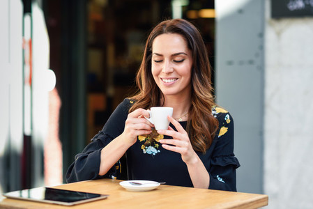 Middle aged woman drinking coffee in an urban cafe bar