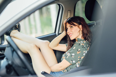 Young woman resting in a white car pulling her feet out the window