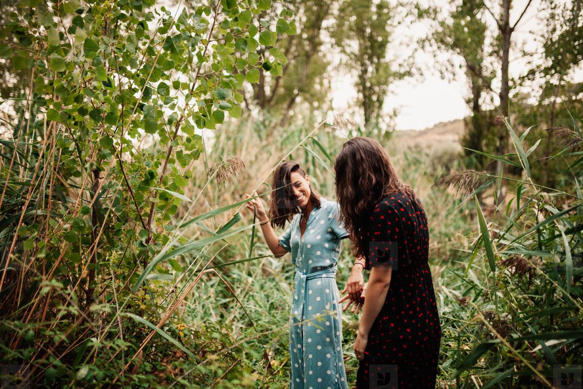 Two young women walking through the field