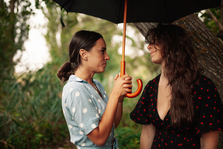 Two young women standing with umbrella on field