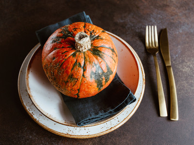 Small pumpkin on a served plate on a table The concept of Thanksgiving dinner