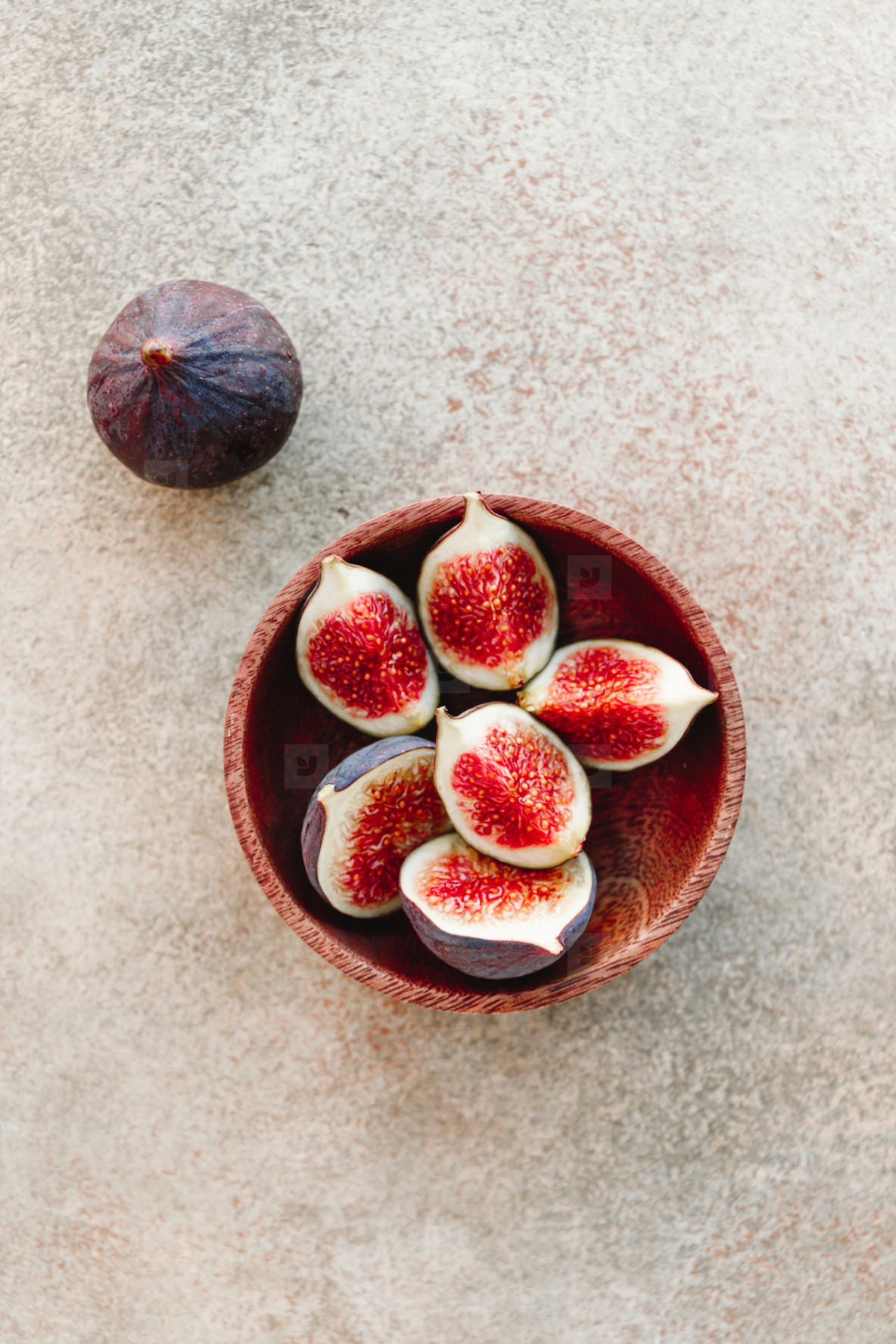Ripe figs in a wooden small bowl on a table  top view