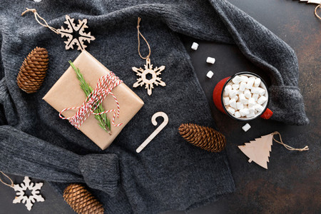 Top view of Christmas or winter time flat lay with hot chocolate  gift box  fir cones  toys on a woolen sweater