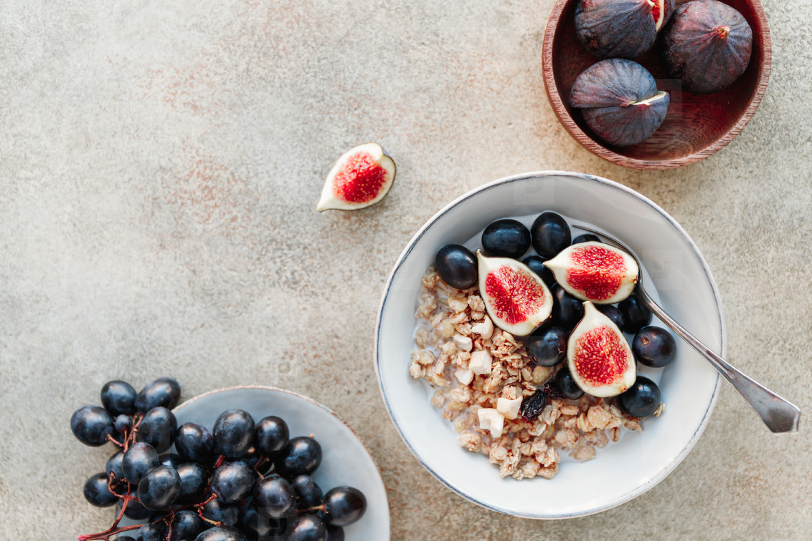 Top view of a breakfast bowl with granola  blue grape and fig slices  Healthy vegan eating  copy space