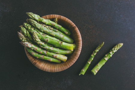 Fresh asparagus in a wooden bowl on a table Top view copy space