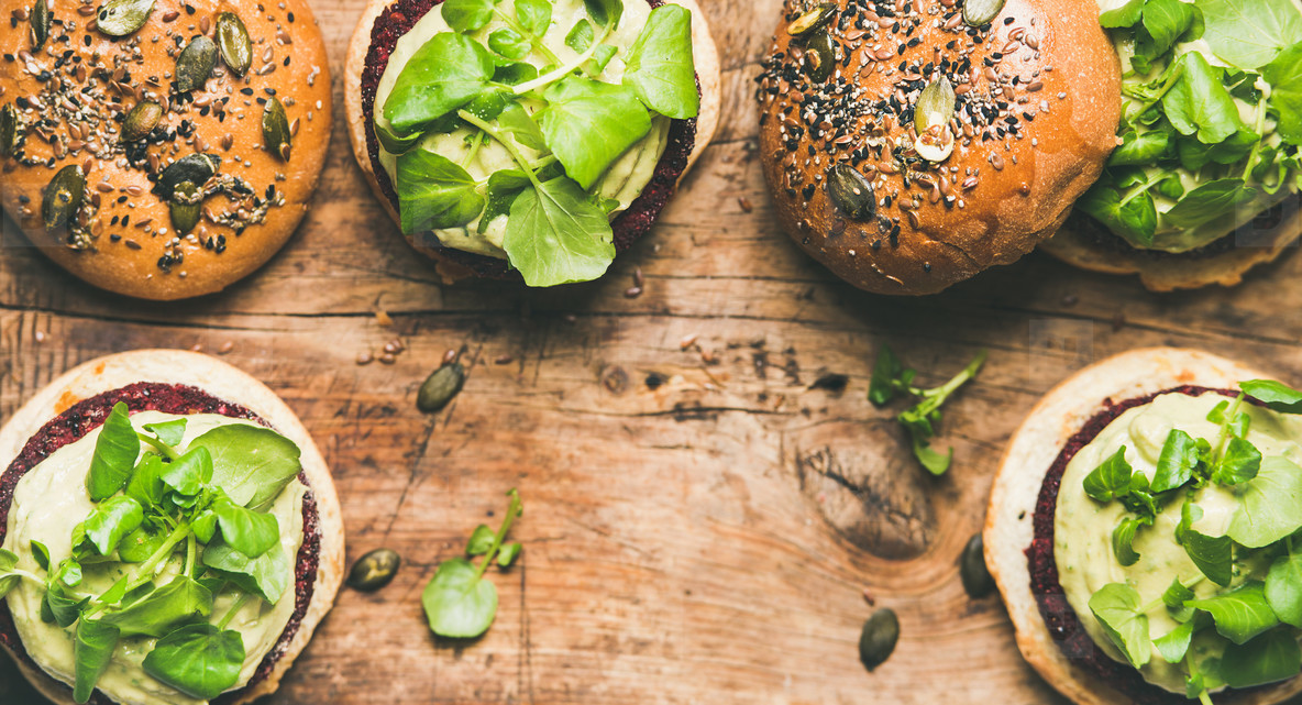 Flat lay of healthy vegan burgers with beetroot patties and sprouts