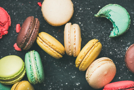 Sweet colorful French macaroon cookies over black background  top view
