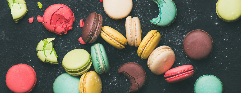 Flat lay of sweet colorful French macaroon cookies variety wide composition