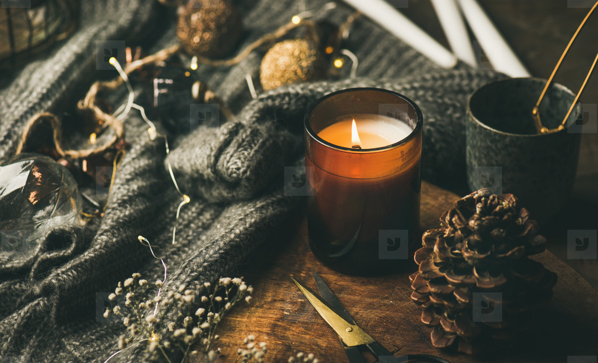 Candle on wooden board  sweater and decoration toys  horizontal composition
