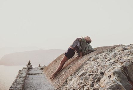 Woman stretching body on stones in Monolithos  Rhodes  Greece