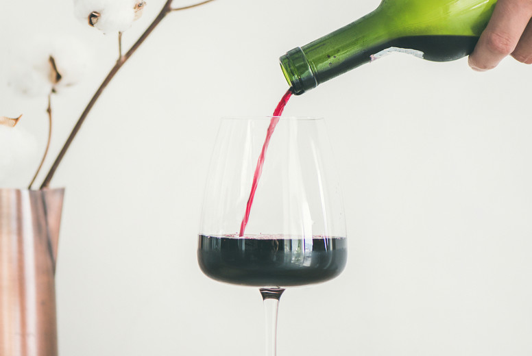 Red wine pouring from bottle in mans hand into wineglass