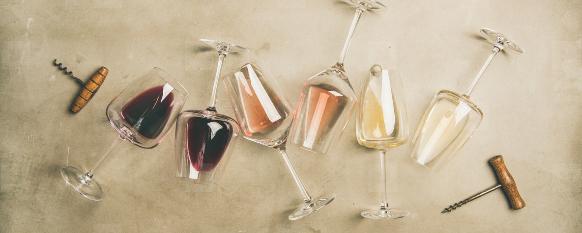 Different wines in glasses and corkscrews over grey background