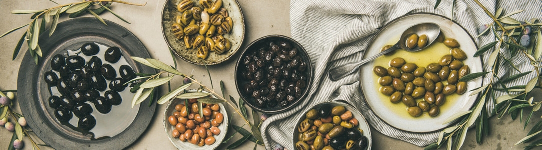Mediterranean pickled olives and olive tree branches wide composition
