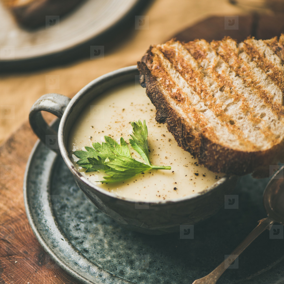 Celery cream soup and toast over linen tablecloth  square crop