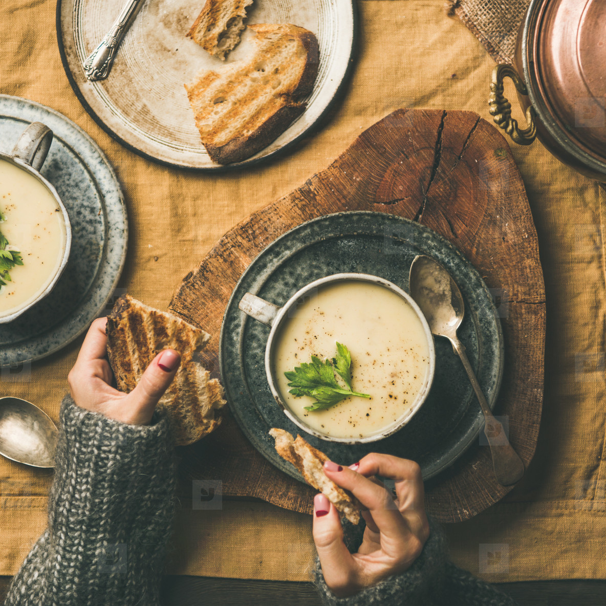 Celery cream soup and female hands with bread  square crop