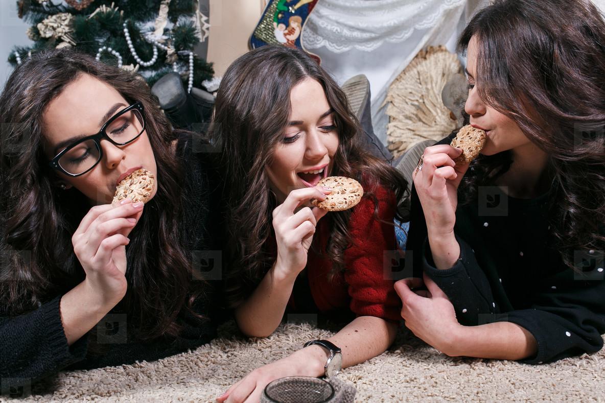 Beautiful girl eating Christmas cookies and drink tea while lyin