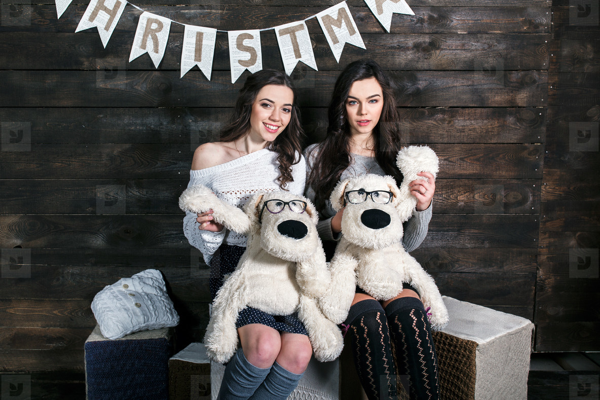 Two charming girls playing with Christmas toys