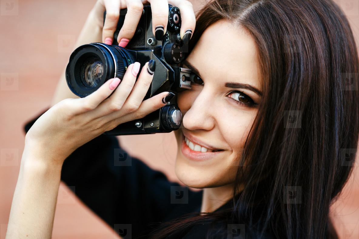 Beautiful female photographer posing with camera