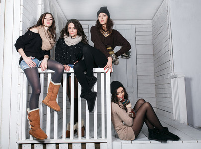 Four stylish models posing sitting on the fence Christmas backg