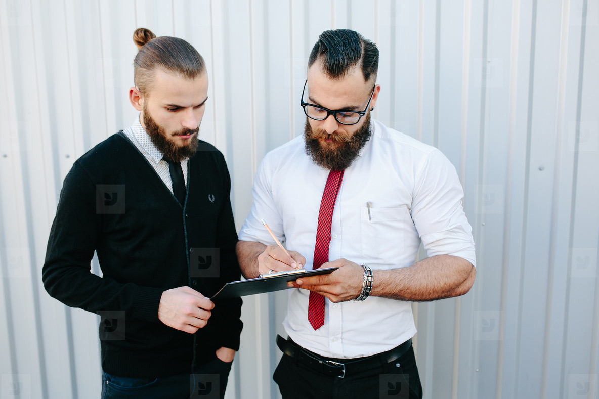 Two bearded businessman signing documents